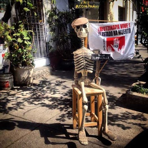 """A skeleton holds a flag reading """"Ayotzinapa lives. The state is dead"""" demanding justice for the disappearing of the 43 students of Ayotzinapa."""