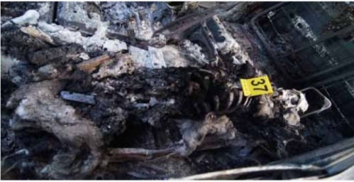One of the victims of the police massacre, his body burned. From the report.